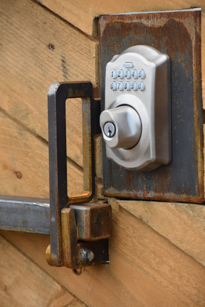 """Shop gate designed for a code/keyed lock, mounted flush with door and braced with 1"""" tube steel."""