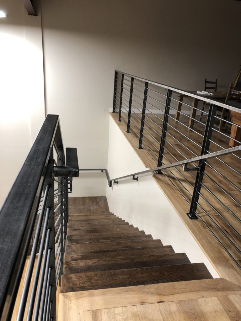 On the second floor of the commercial property there's a pretty great mezzanine, and this guardrail needed to maximize stair tread space. Thus, we created footers for each post and lagged them into the floor.